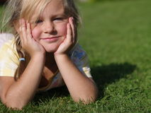Little girl lying on grass. Little girl dressed in yellow t-shirt lying on grass royalty free stock photo