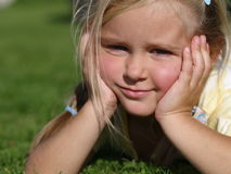 Little girl lying on grass. Little girl dressed in yellow t-shirt lying on grass royalty free stock photos