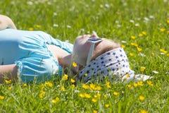 Little girl lying on grass Stock Image