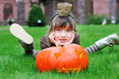 Little girl lying on a grass with big pumpkin Royalty Free Stock Images
