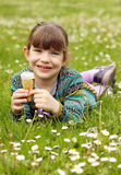 Little girl lying on grass and eat ice cream Royalty Free Stock Images