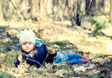Little girl lying on grass in forest. Stock Images