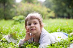 Little girl lying in grass royalty free stock images
