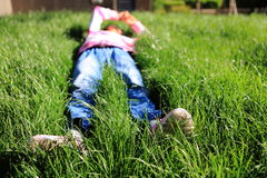 The little girl lying on the grass Stock Images