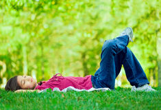 Little girl lying on grass. Lawn sleeping , one leg crossed over the other Stock Image