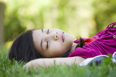 Little girl lying on grass Stock Photo