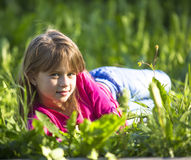 Little girl lying in the grass outdoors Stock Photography