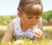 Little girl lying on grass in the park Stock Photo