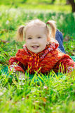 Little girl lying on the grass in the park Stock Image