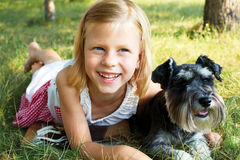 little girl lying on the grass in the park, beside her dog Royalty Free Stock Photography