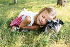 Little girl lying on the grass in the park, beside her dog Stock Image