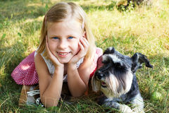 Little girl lying on the grass in the park, beside her dog Stock Photos