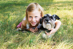 Little girl lying on the grass in the park, beside her dog Royalty Free Stock Photos