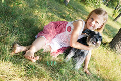 little girl lying on the grass in the park, beside her dog Stock Images