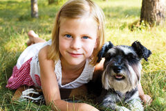 Little girl lying on the grass in the park, beside her dog Stock Photography