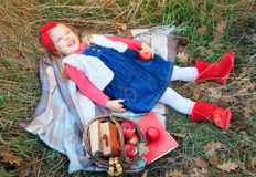 Little girl lying in grass on a plaid with a basket of fruit. Stock Images