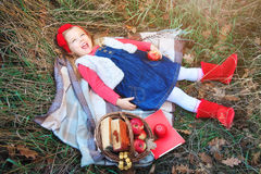 Little girl lying in grass on a plaid with a basket of fruit. Stock Photo
