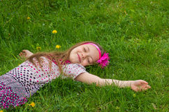 Little girl lying in grass Stock Photo