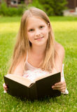 Little girl lying on grass and read book Royalty Free Stock Photo