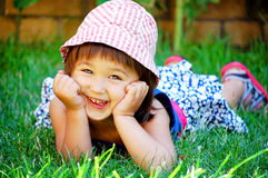 Little girl lying on the grass and smiling Stock Images