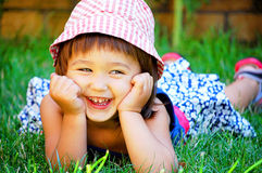Little girl lying on the grass and smiling Royalty Free Stock Image
