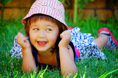 Little girl lying on the grass and smiling Royalty Free Stock Photos