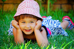 Little girl lying on the grass and smiling Royalty Free Stock Photography