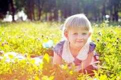 Little girl lying on the grass Stock Photos