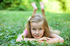 Little girl is lying on green grass Royalty Free Stock Images