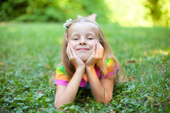 Little girl is lying on the green grass Stock Photo