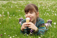 Little girl lying on green grass and eat ice cream Stock Photo