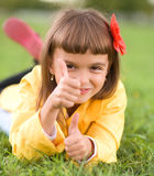 Little girl lying on green grass. Is showing thumb up gesture Royalty Free Stock Image