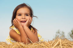 Little girl lying on a haystack Stock Photography
