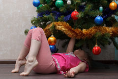 Little girl lying on her back under Christmas tree Royalty Free Stock Image
