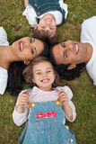 Little girl lying with her family in a park Stock Photography
