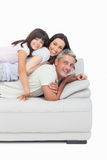 Little girl lying on her parents on sofa Royalty Free Stock Image