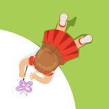 Little girl lying on her stomach and painting a purple butterfly, top view of child on the floor royalty free illustration