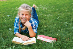 Little girl is lying on her stomach reading on the grass. Cute little girl is lying on her stomach reading on the grass Royalty Free Stock Photo