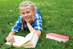 Little girl is lying on her stomach reading on the grass. Cute little girl is lying on her stomach reading on the grass Stock Photo
