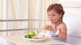 Little girl lying in hospital bed eating her lunch Stock Photo