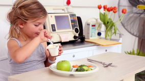 Little girl lying in hospital bed eating her lunch Stock Image