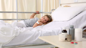 Little girl lying in hospital bed looking at medicine stock footage