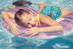 Little girl lying on the  inflatable rubber circle  in the swimm Stock Photo