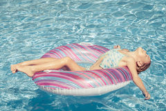 Little girl lying on the  inflatable rubber circle  in the swimm Stock Photos