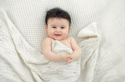 Portrait of a baby. Little girl lying on a knitted coverlet Royalty Free Stock Photos