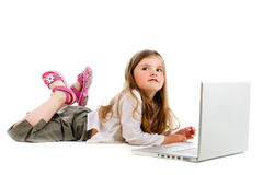 Little girl lying with laptop Royalty Free Stock Images