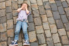 Little girl lying on the pavement. Covering eyes with hands stock images
