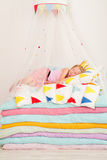 Little girl lying on a pile of mattresses Royalty Free Stock Photos