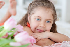 Little girl lying with pink tulips Stock Photography