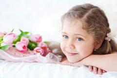 Little girl lying with pink tulips Royalty Free Stock Images